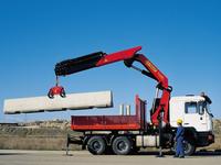 MAN Truck mit Palfinger Kran PK 36002 beim Heben einer Beton-Leitplanke
